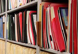 Annual report folders organized on shelves